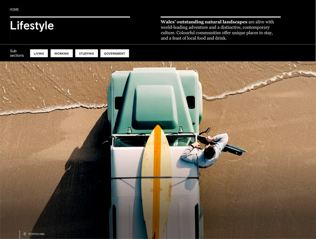 Shows the heading of an article for wales.com and visitwales.com. The text is places at the top followed by tags in the next row. Below those two elements there's a large image with a man coming out of a jeep in the beach. The jeep has a surfboard on the roof.
